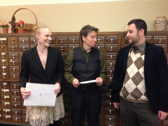 Theatre students Emily Clark (left) and Dan Venning (right) offer the Kirle Gift to Chief Librarian Polly Thistlethwaite (middle).